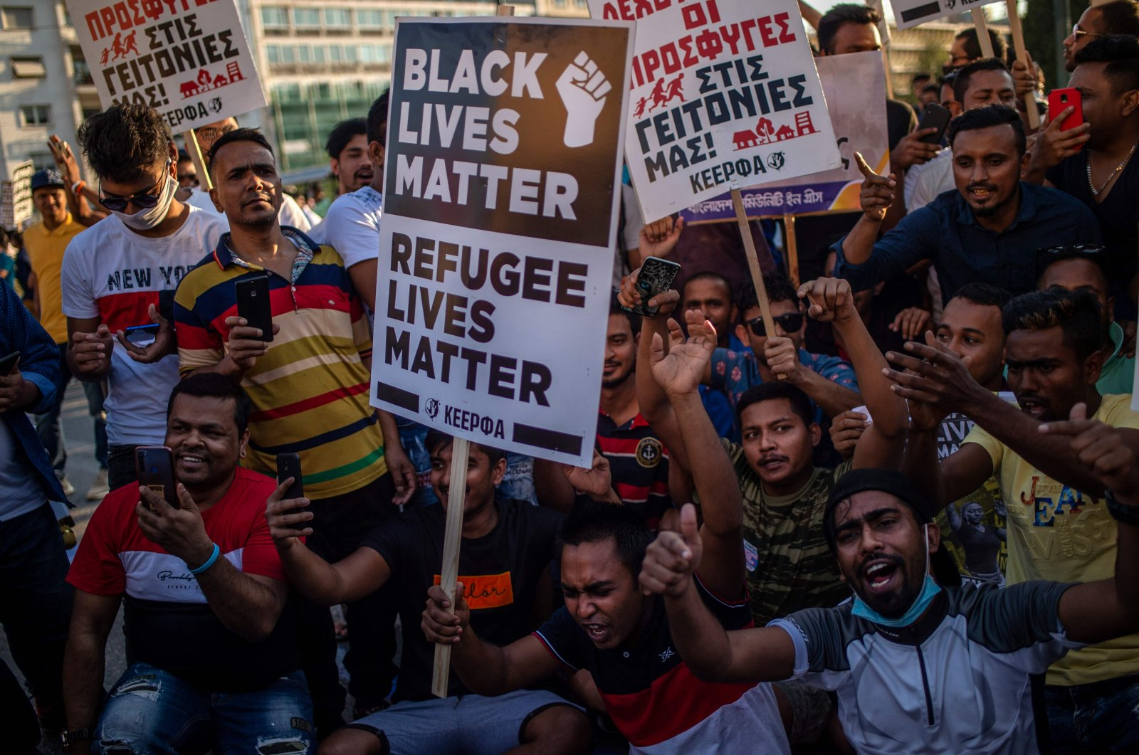 """A protester holds a placard reading """"Black Lives Matter, Refugee Lives Matter"""" during a demonstration to demand rights and housing for refugees and migrants in Greece, June 26, 2020. (AFP Photo)"""