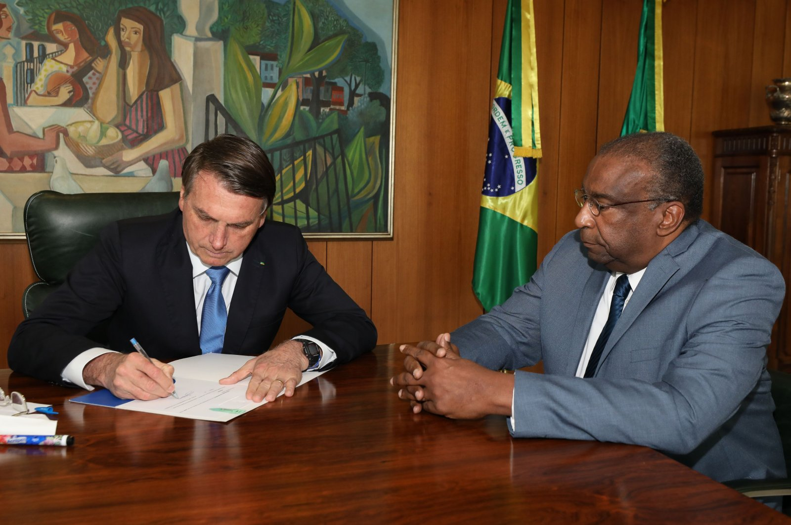 A handout photo released by the Brazilian Presidency press office shows President Jair Bolsonaro (L) and his new Minister of Education Carlos Alberto Decotelli, the first black minister in his Cabinet, at Planalto Palace in Brasilia, Brazil, June 26, 2020. (AFP Photo / Brazilian Presidency)