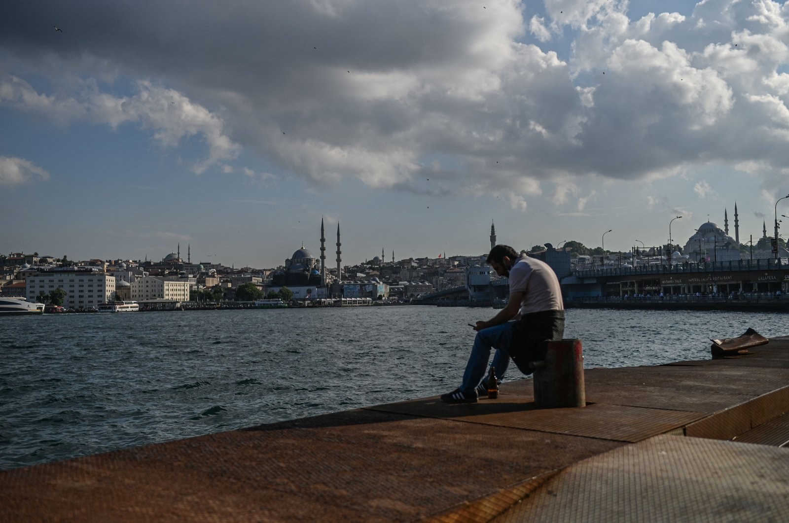 A man sits near the shore of the Golden Horn strait Süleymaniye Mosque (R), as the New Mosque (L) is seen in the background, Istanbul, June 24, 2020. (AFP Photo)