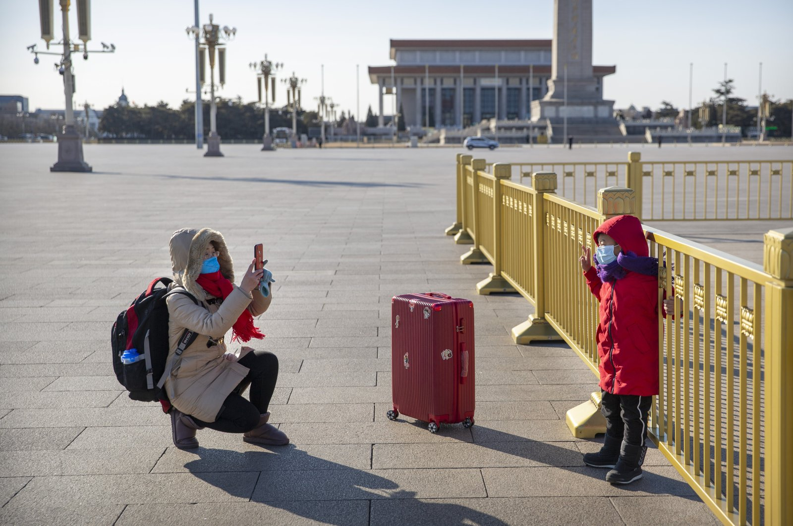 A woman wearing a face mask takes a photo of a child on a nearly empty Tiananmen Square in Beijing, Tuesday, Feb. 4, 2020. (AP Photo)