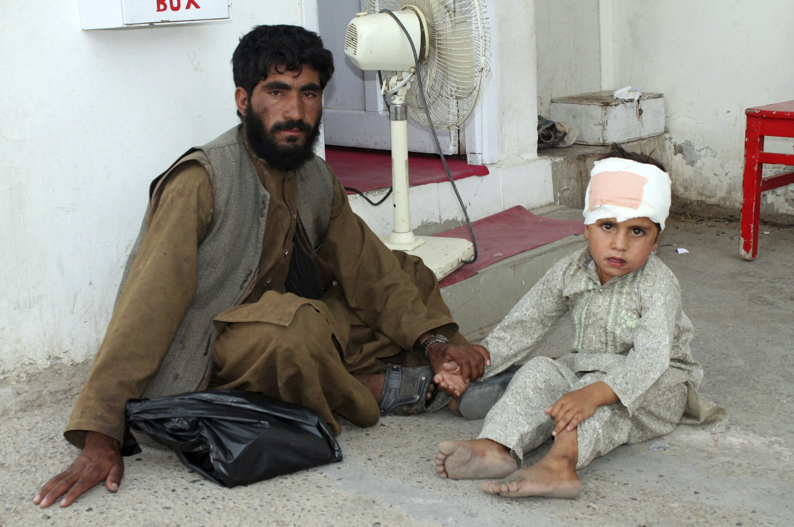 A boy who was injured boy in a deadly attack on a market sits on the ground at a hospital in Helmand province, June 29, 2020. (AP Photo)