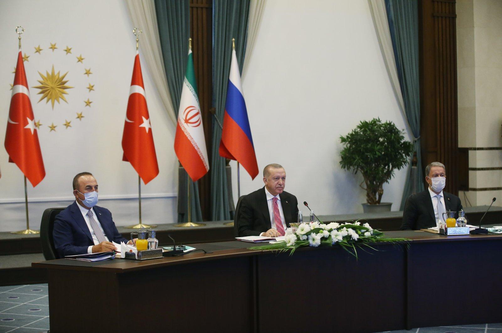 Turkish Foreign Minister Mevlüt Çavuşoğlu (L), President Recep Tayyip Erdoğan (C) and Defense Minister Hulusi Akar (R) during the Turkey-Russia-Iran videoconference summit under the Astana process, July 1, 2020. (AA Photo)