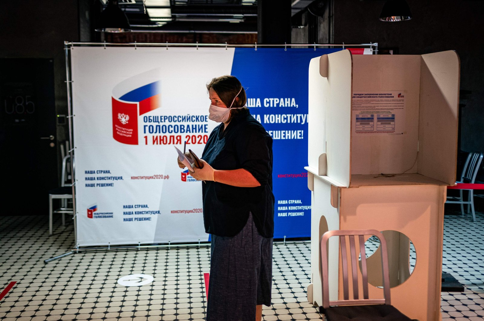 A woman wearing a face mask and gloves - a measure against the spread of the coronavirus disease - prepares to cast her ballot in a nationwide vote on constitutional reforms at a polling station inside the GULAG History Museum in Moscow on July 1, 2020. (AFP Photo)