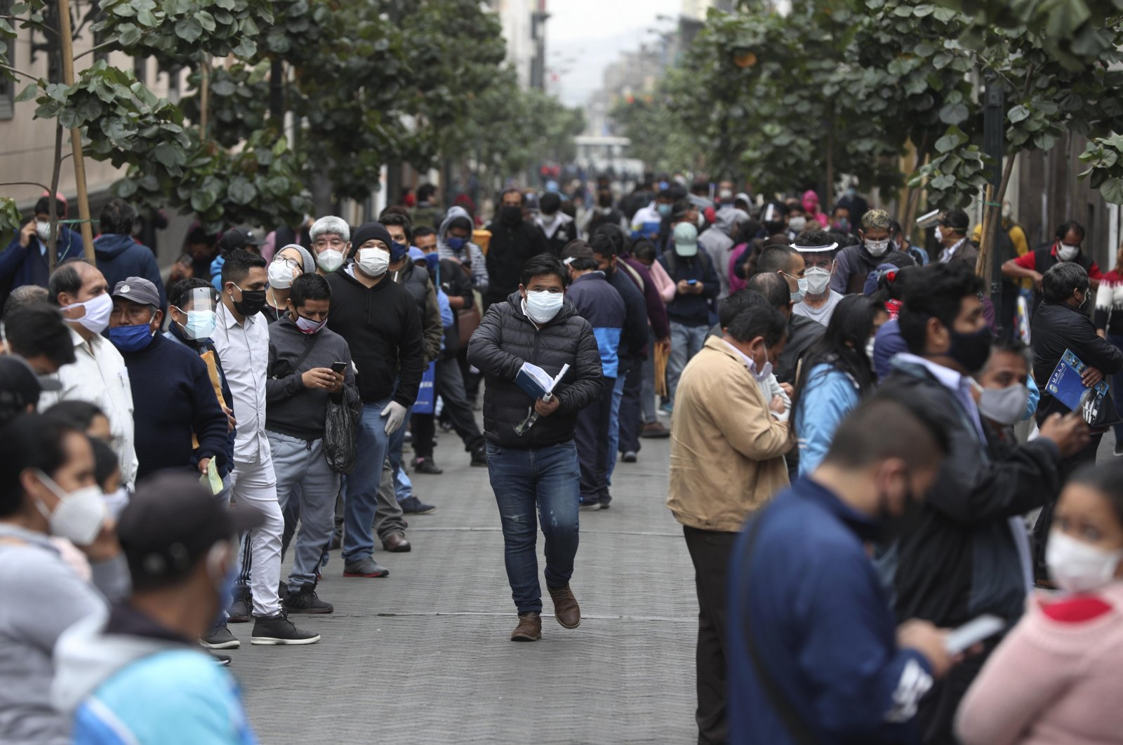 People wait in line for some businesses to reopen in downtown Lima, Peru, July 1, 2020. (AP Photo)