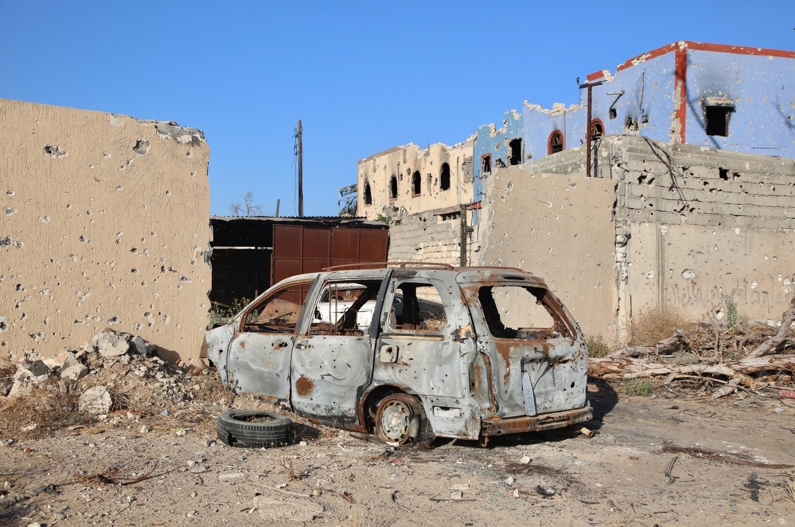 A destroyed vehicle is pictured in front of rundown buildings in residential areas in southern Tripoli liberated from Khalifa Haftar's militias, June 27, 2020. (AA Photo)