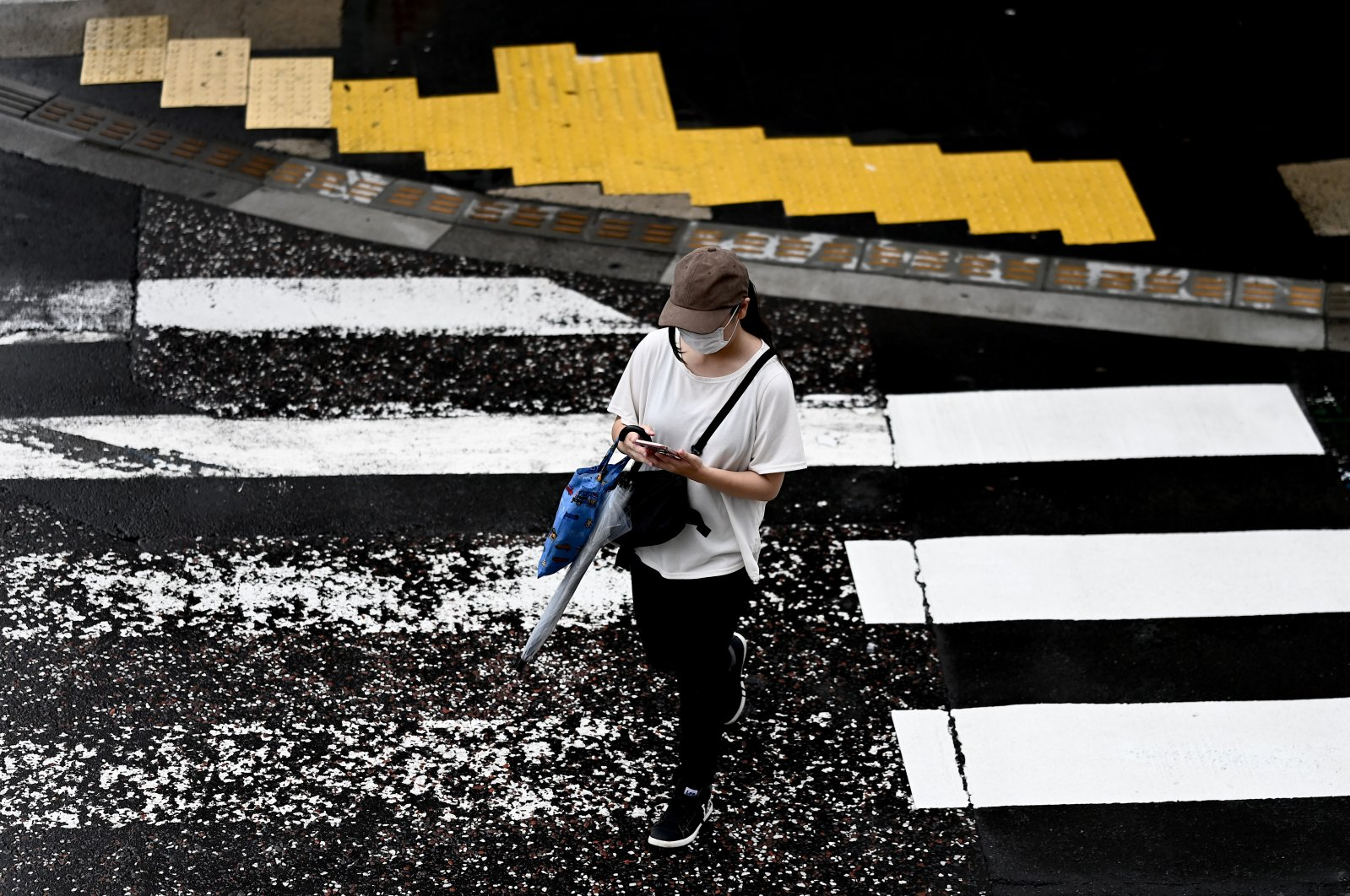 A woman uses her phone while crossing a street in Yamato, Kanagawa prefecture, July 1, 2020. (AFP Photo)