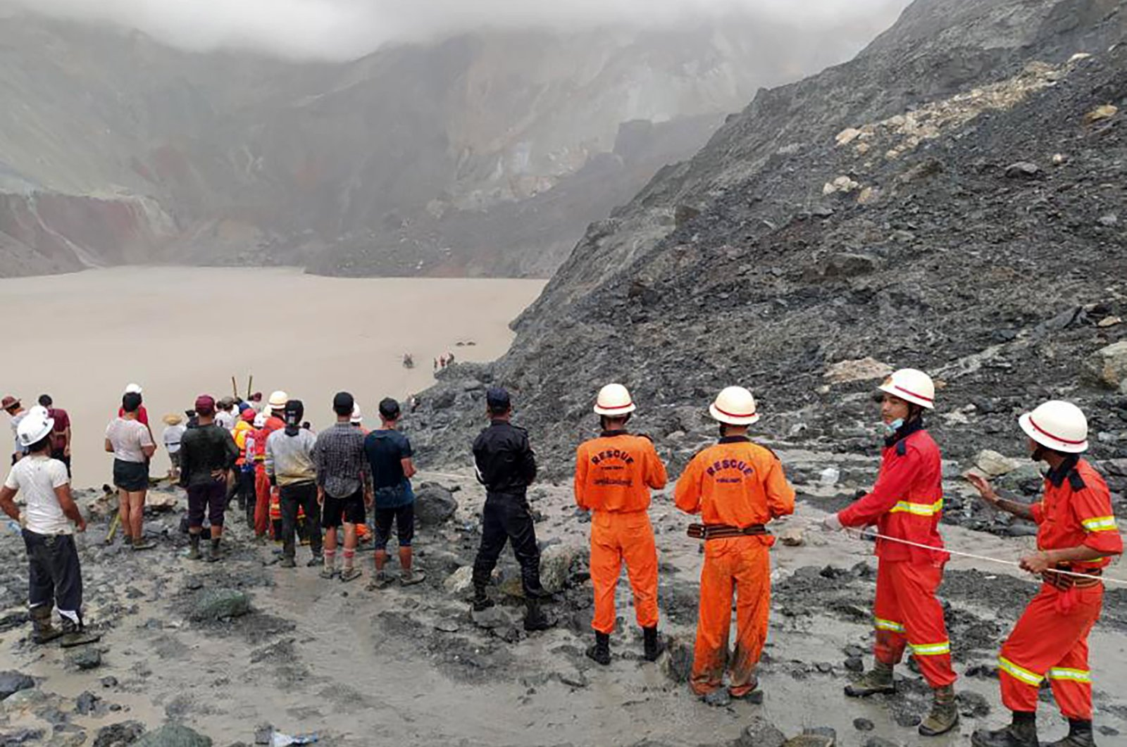 A handout photo made available by the Myanmar Fire Services Department shows rescue workers searching for people after a landslide accident at a jade mining site in Hpakant, Kachin State, Myanmar, July 2, 2020. (Myanmar Fire Services via EPA)