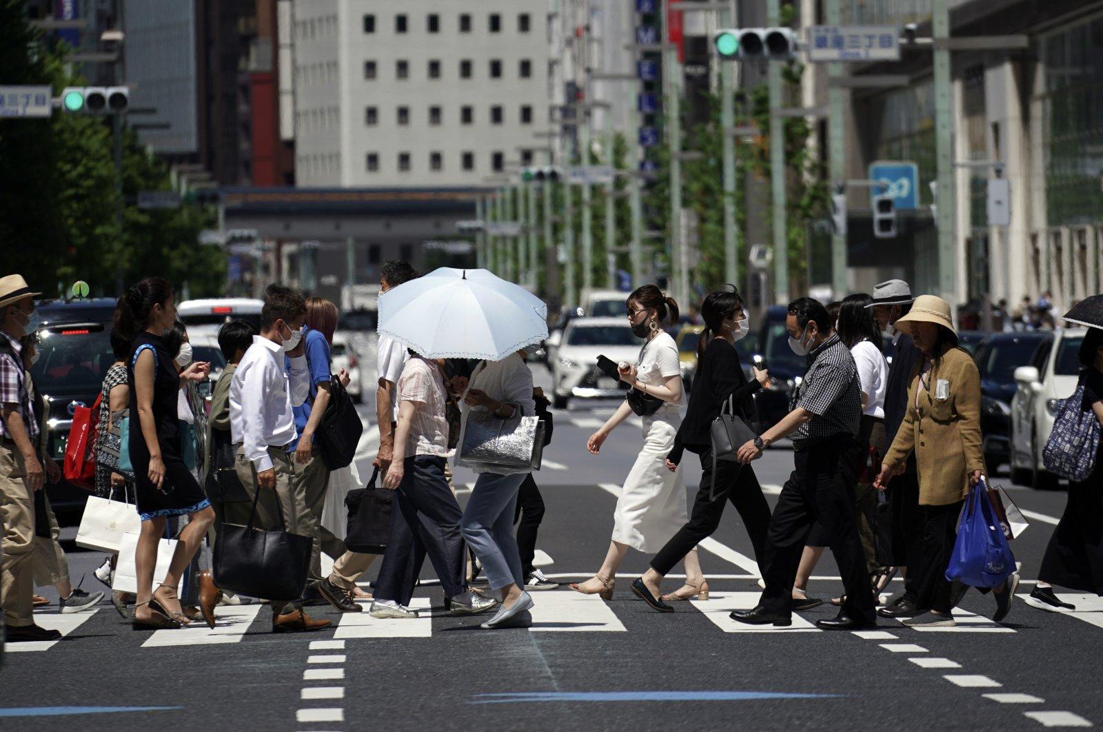 People walk on a pedestrian crossing in Tokyo, July 2, 2020. (AP Photo)