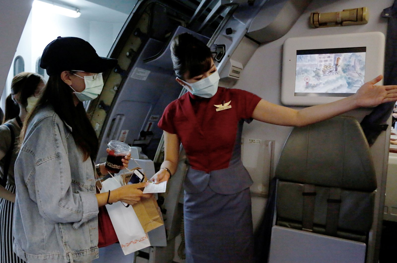 """People board a plane as they take part in a """"fake"""" travel experience at Songshan airport in Taipei, Taiwan, July 2, 2020. (Reuters Photo)"""