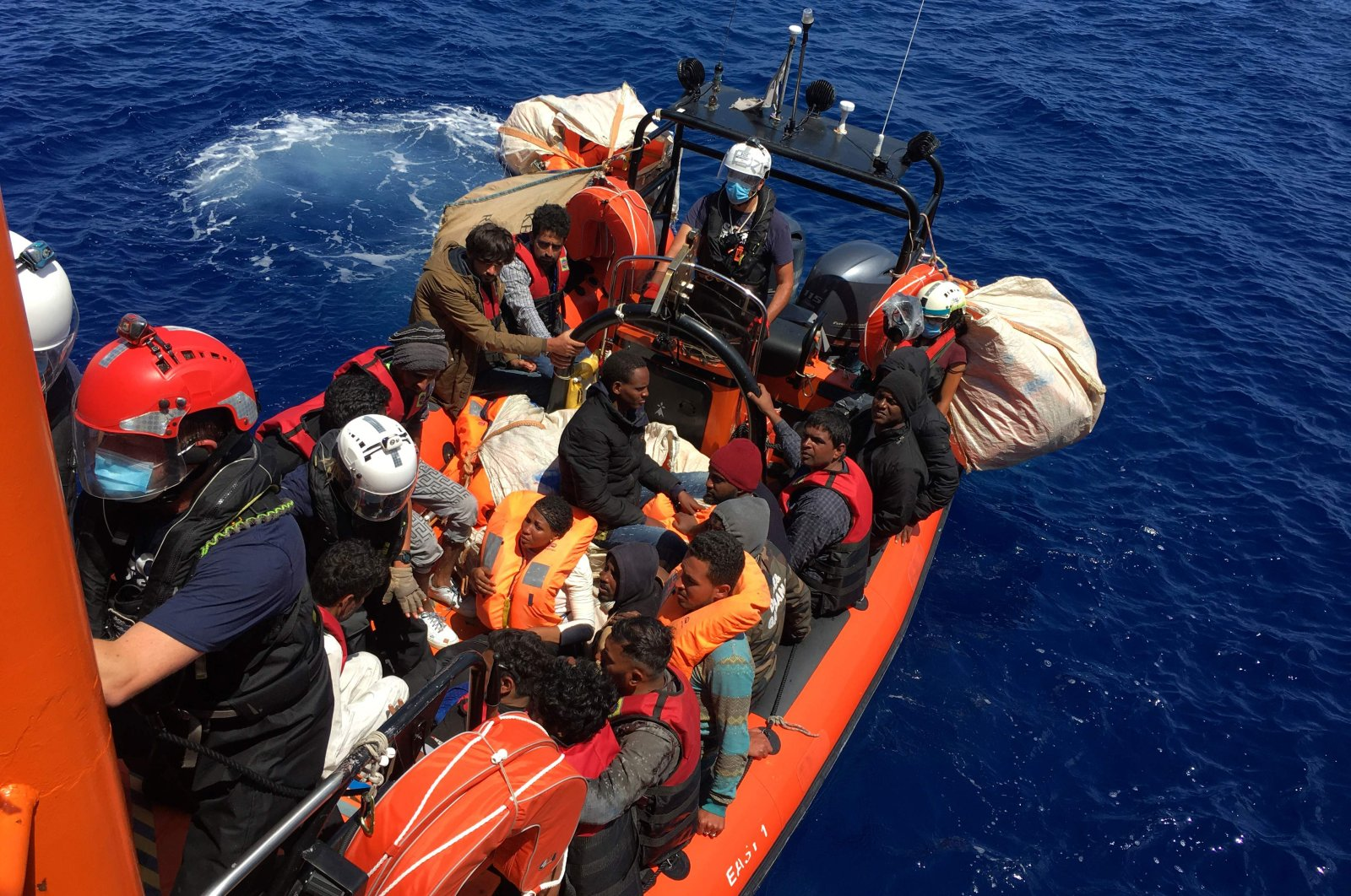 Some of the 51 migrants, who were drifting on a wood boat, are rescued by members of the French NGO SOS Mediterranee's boat Ocean Viking, off the coast of Lampedusa island, June 25, 2020. (AFP Photo)