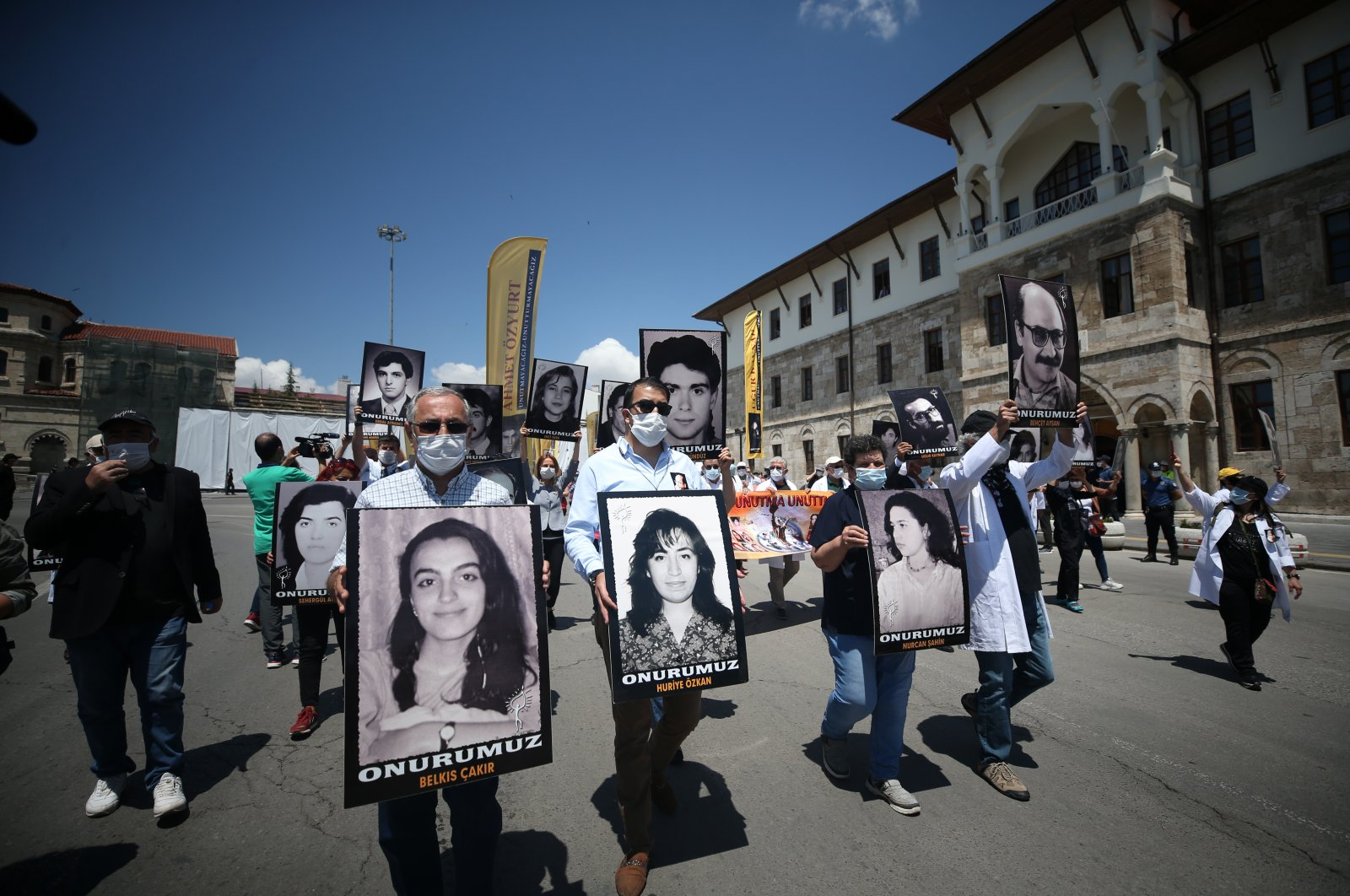 People carrying photos of victims march on the street, in Sivas, Turkey, July 2, 2020. (AA Photo)