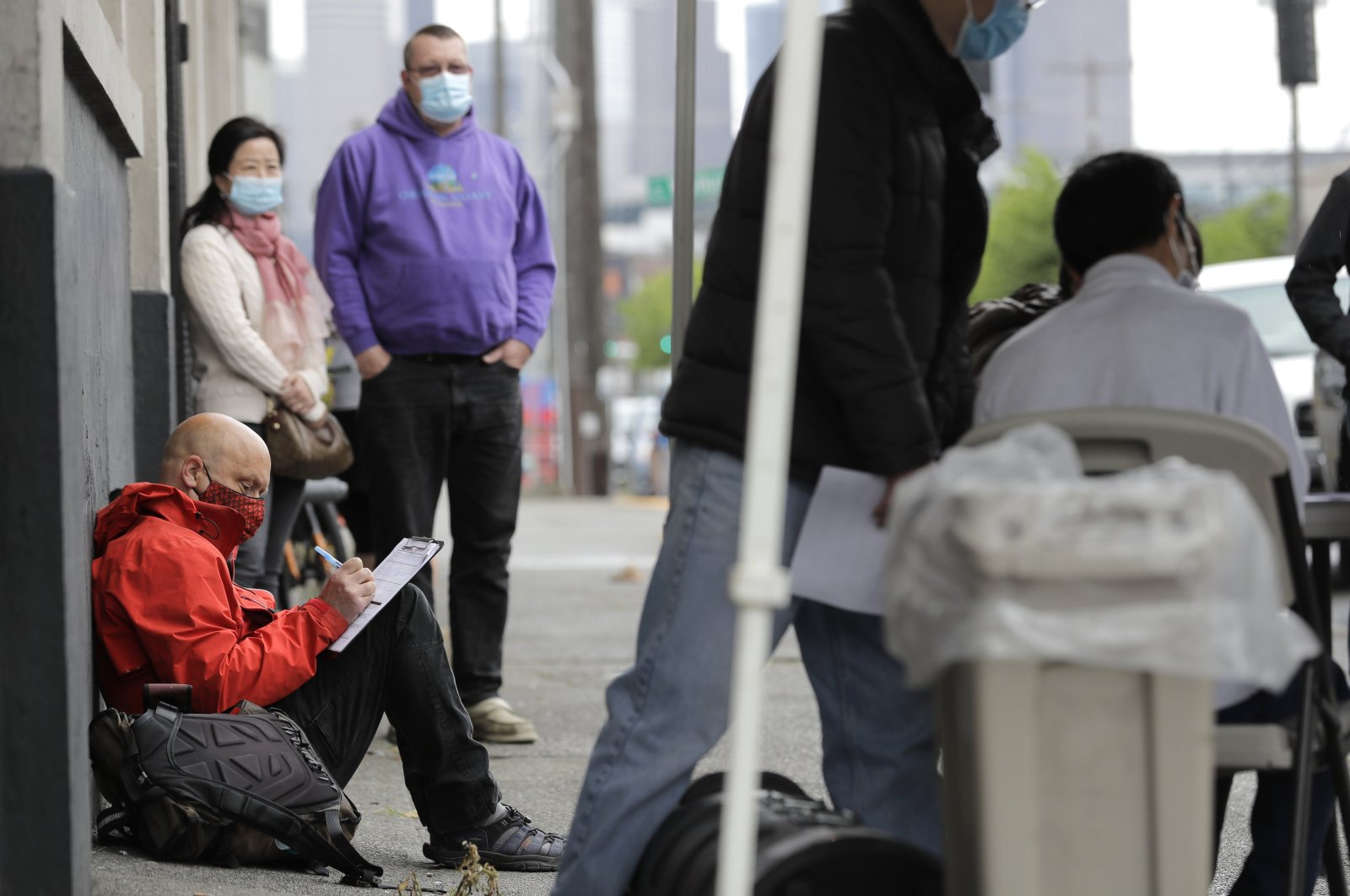 A man (L) fills out a job application during a walk- and drive-up job fair in Seattle for clothing maker Outdoor Research's new line of face masks and other personal protection equipment, Washington state, U.S., May 16, 2020. (AP Photo)