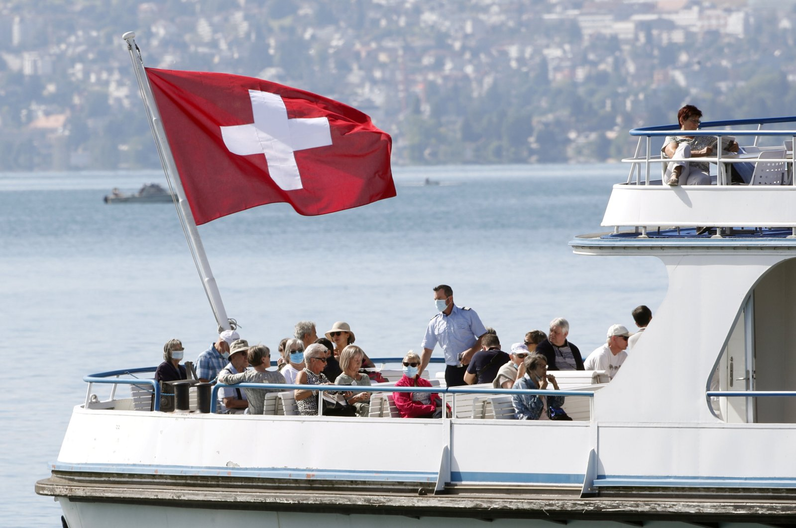 Switzerland's national flag flies above passengers as tourist vessel Limmat sails on Lake Zurich, as the coronavirus disease continues, in Zurich, June 30, 2020. (REUTERS)