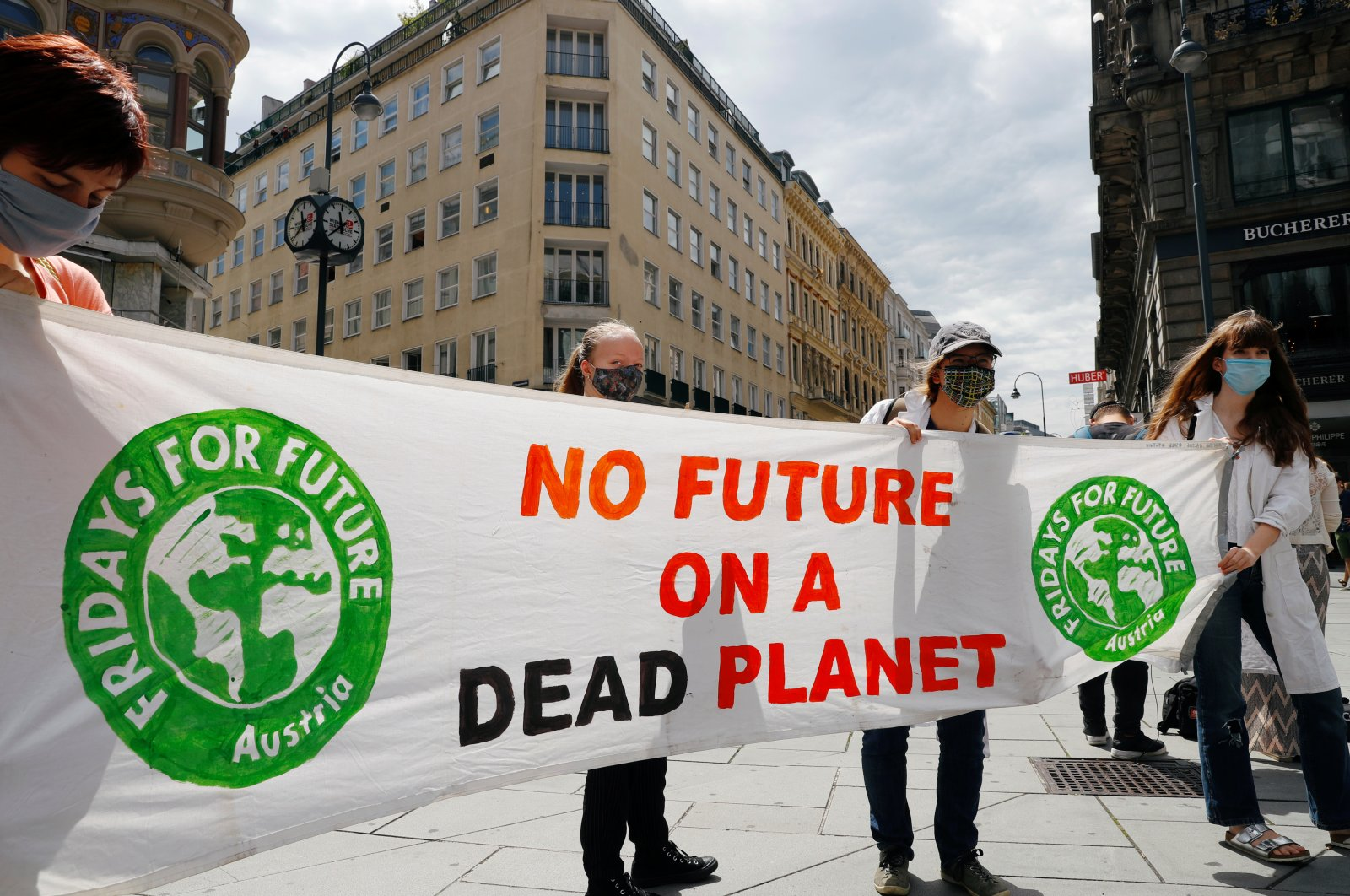People hold a banner during a protest march to call for action against climate change, as the spread of the coronavirus disease (COVID-19) continues, in Vienna, Austria, June 26, 2020.(Reuters Photo)