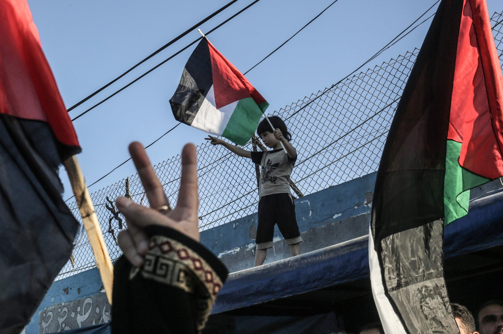 A Palestinian boy waves a national flag during a demonstration against Israel's West Bank annexation plans, in Khan Yunis in the southern Gaza Strip, July 2, 2020. (AFP)
