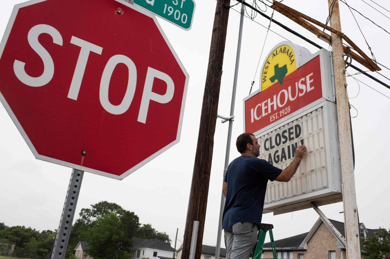 """Bar owner Petros J Markantonis changes the marquee outside his bar to """"Closed Again"""" at the West Alabama Ice House in Houston, Texas, June 26, 2020. (AFP)"""