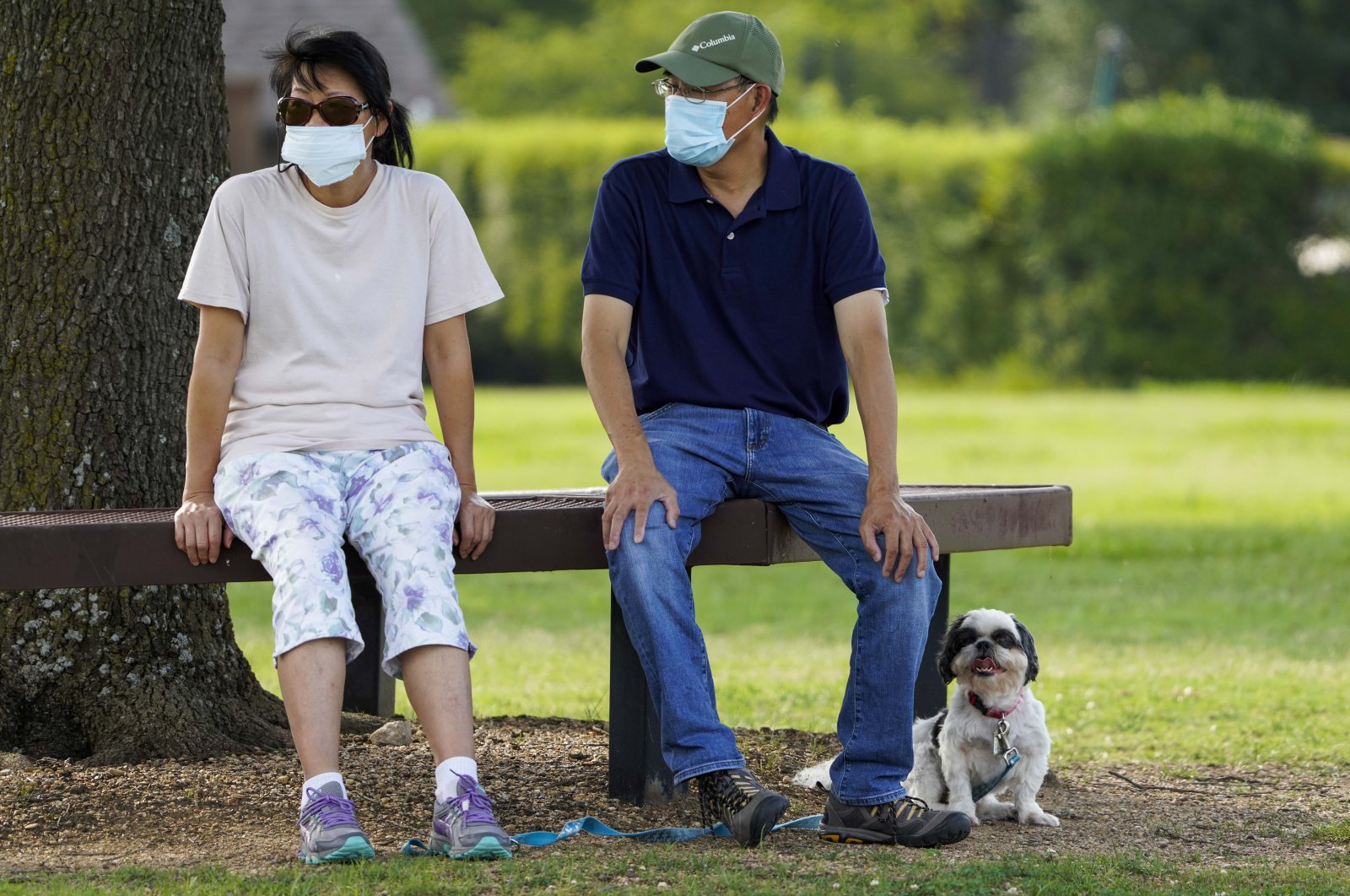 People wear face masks as they sit with their dog at Custer Park in Richardson, Texas, U.S., July 2, 2020. (The Dallas Morning News via AP)