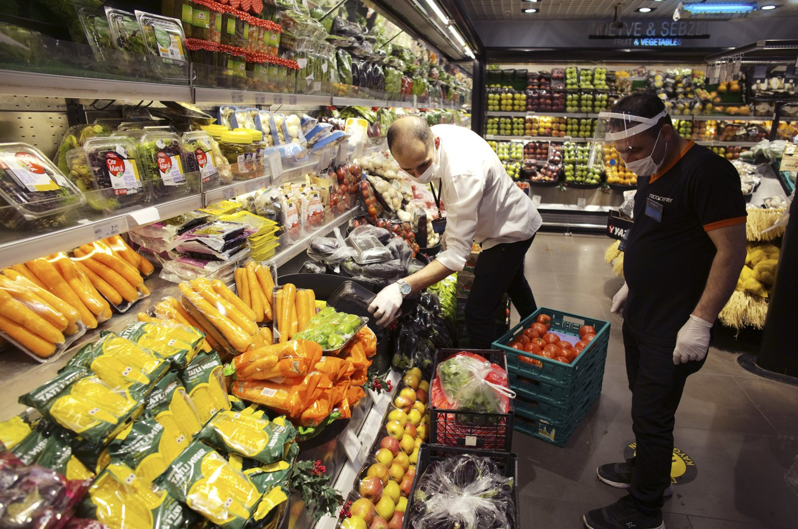 People wearing face masks to protect against the coronavirus shop for food at a grocery store, Ankara, Turkey, May 22, 2020. (AP Photo)