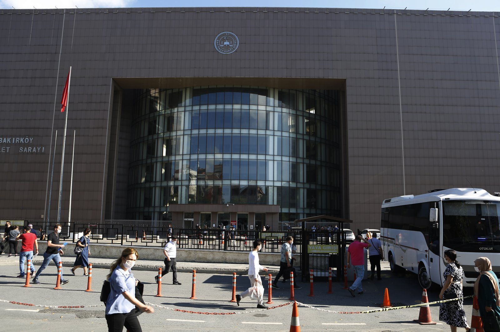 People walk outside a court building in Istanbul where the trial began for defendants accused of smuggling former Nissan Chairman Carlos Ghosn out of Japan to Lebanon, via Turkey, Friday, July 3, 2020. (AP Photo)
