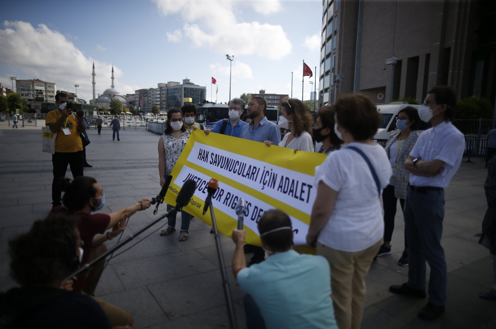 """Supporters of the defendants in the """"Büyükada trial"""" talk to reporters outside the courthouse in Istanbul, Turkey, July 3, 2020. (AP Photo)"""