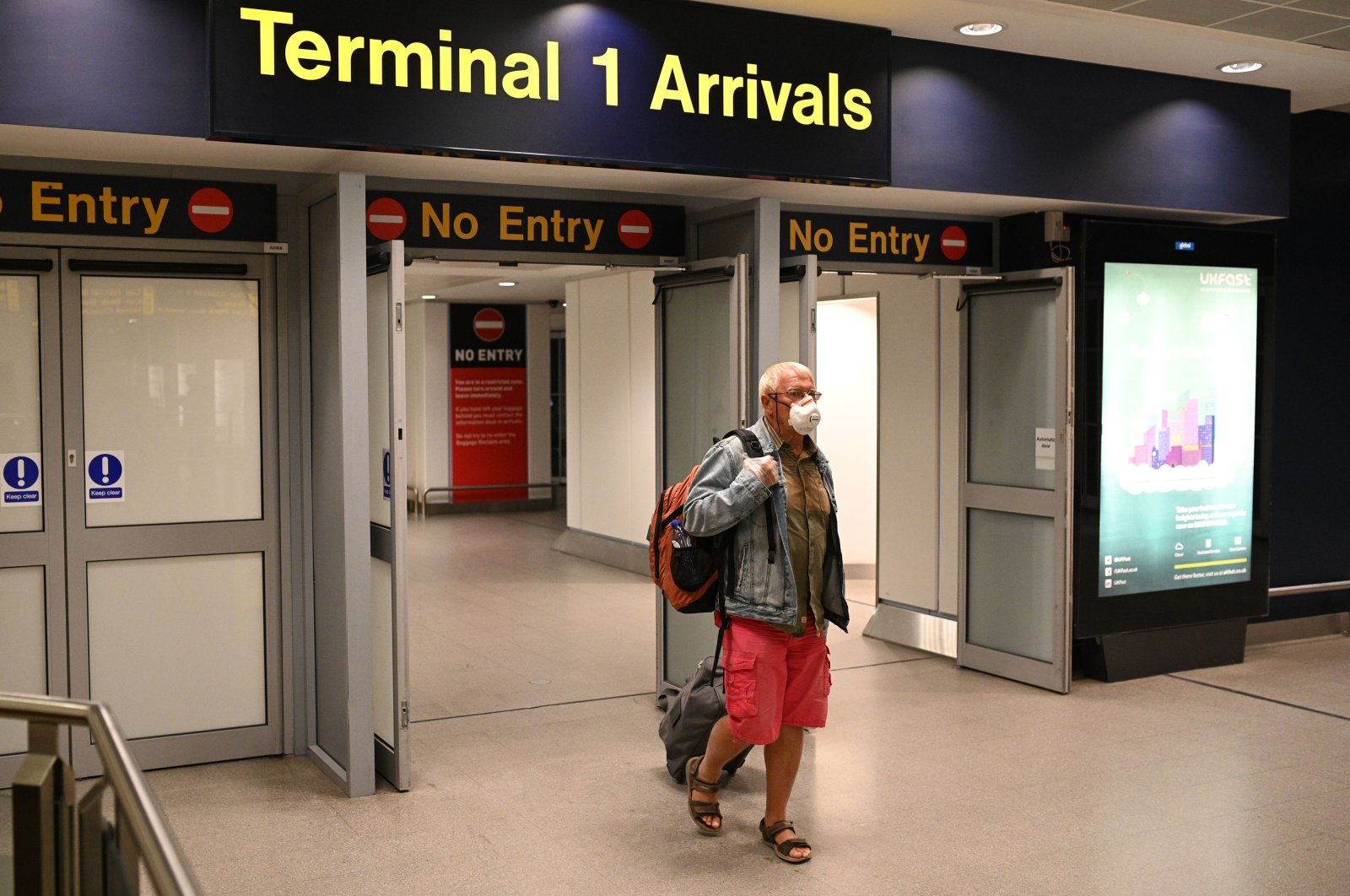 In this file photo taken on June 8, 2020 a passenger wearing PPE (personal protective equipment), including a face mask as a precautionary measure against COVID-19, arrives at Terminal 1 of Manchester Airport in north west England. (AFP Photo)
