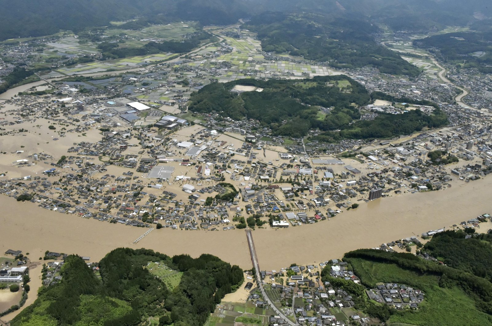 Areas are inundated in muddy waters that gushed out from the Kuma River in Hitoyoshi, Kumamoto prefecture, southwestern Japan, Saturday, July 4, 2020. (Kyodo News via AP)