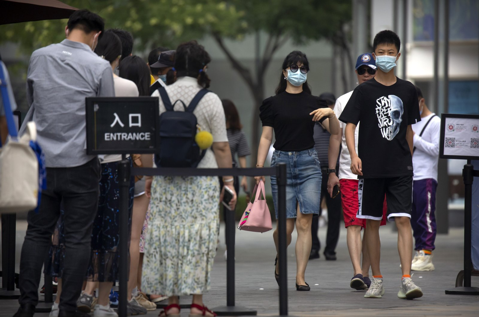 People wearing face masks to protect against the new coronavirus walk past a line of people waiting to show the results of a smartphone health check app before they can enter an outdoor shopping mall in Beijing, Saturday, July 4, 2020. (AP Photo)