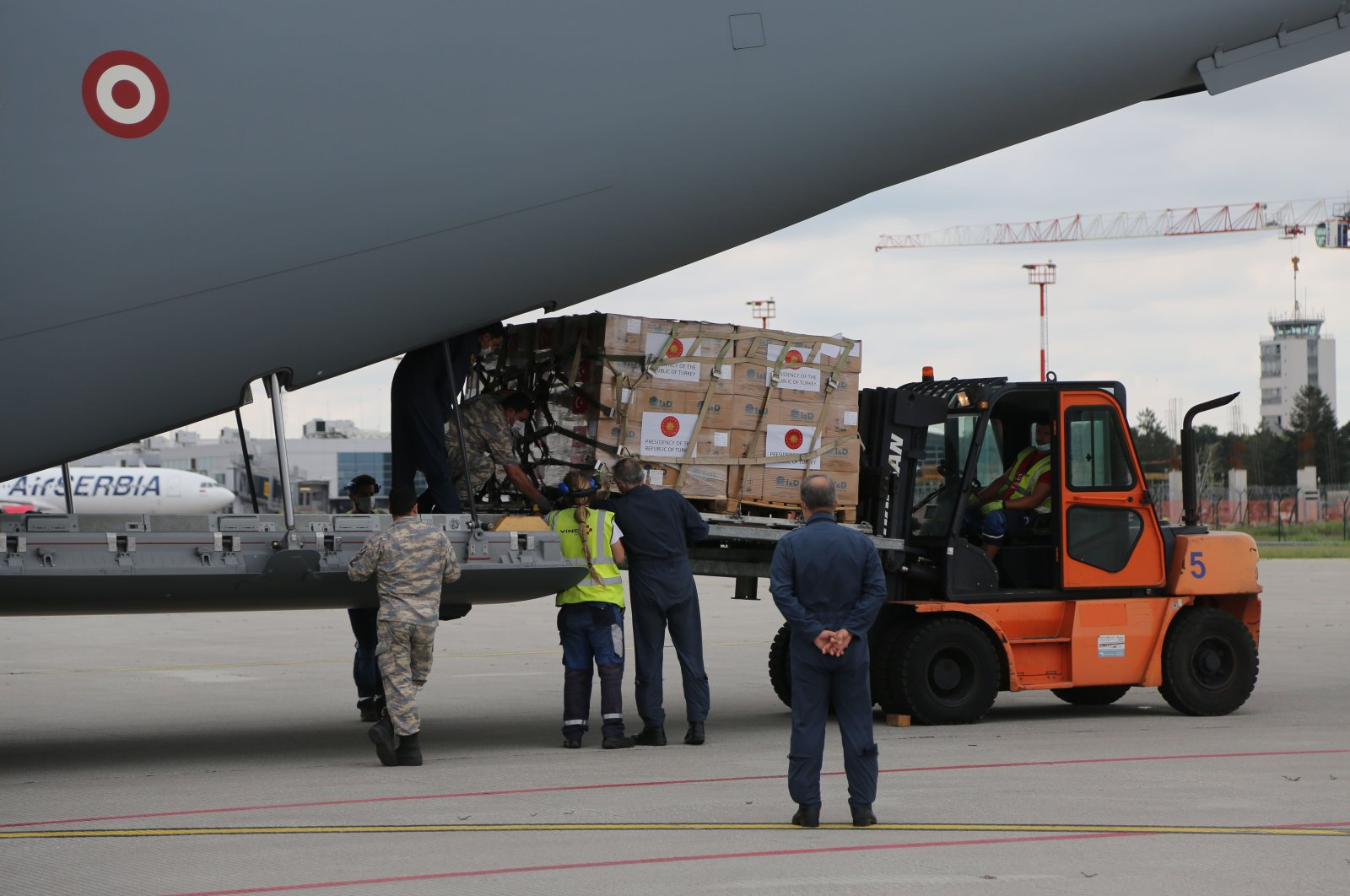 Airport workers unload Turkish equipment to be used in Serbia's fight against coronavirus at Nikola Tesla Airport, Belgrade, July 4, 2020. (AA Photo)