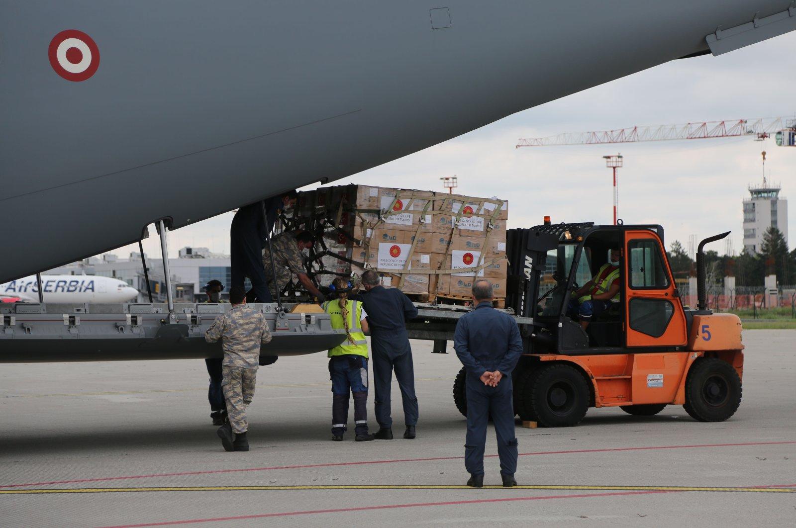 Airport workers unload Turkish equipment to be used in Serbia's fight against coronavirus at Nikola Tesla Airport, Belgrade, July 4, 2020. (AA Photo)