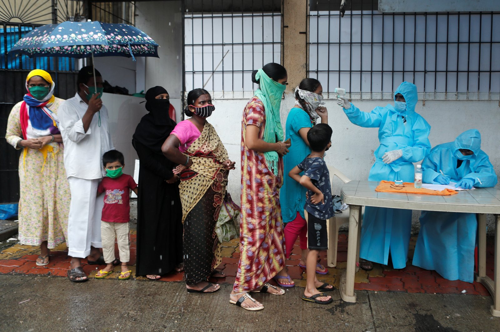 People stand in a queue as a healthcare worker checks the temperature of a resident using an electronic thermometer during a medical campaign for the coronavirus disease (COVID-19) in Mumbai, India, July 4, 2020. (Reuters Photo)