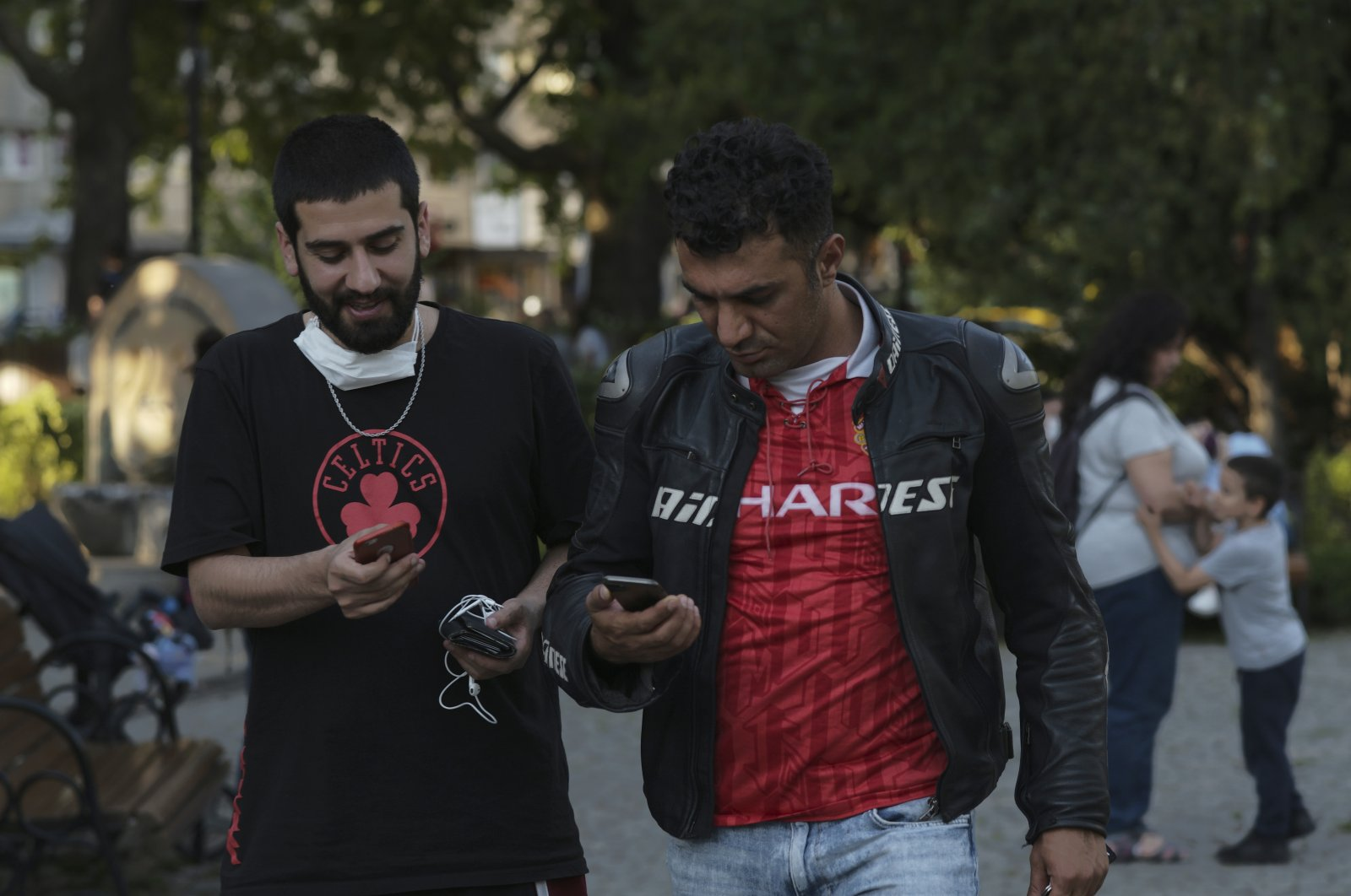 Two men without face coverings speak as they check their mobile phones in a public garden, in Ankara, Turkey, Tuesday, June 30, 2020. (AP Photo)