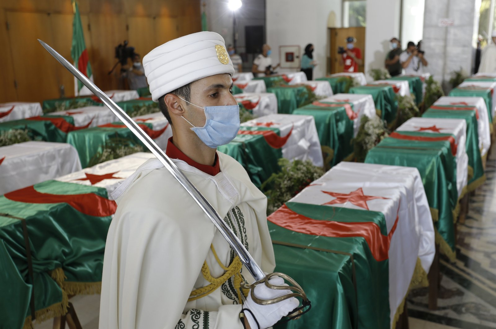 A soldier guards the remains of 24 Algerians at the Moufdi-Zakaria culture palace in Algiers, Friday, July, 3, 2020. (AP Photo)