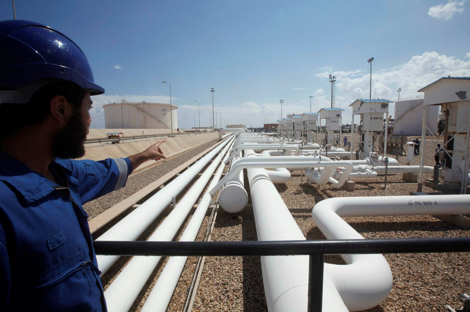 A worker gestures toward pipelines at the port and Zawiya Oil Refinery, Aug. 22, 2013. (Reuters File Photo)