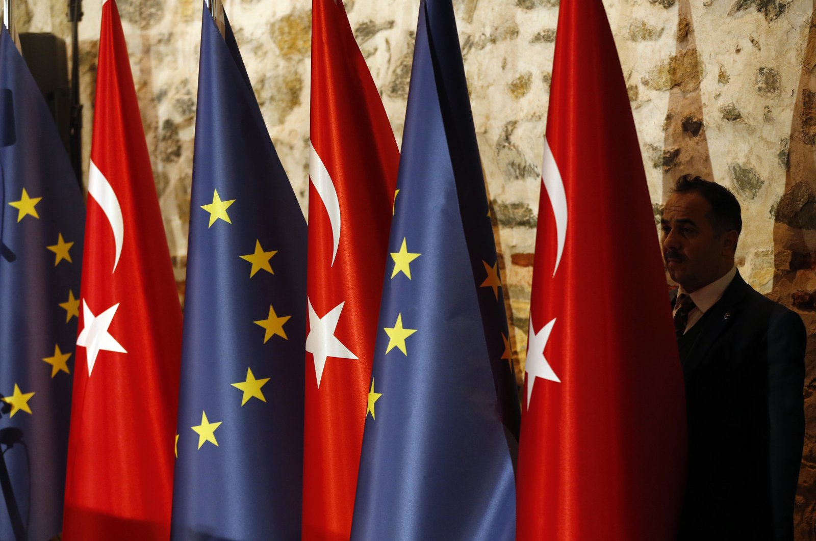 An official adjusts Turkey's and the European Union flags prior to the opening session of a high-level meeting between EU and Turkey, Istanbul, Feb. 28, 2019. (AP Photo)