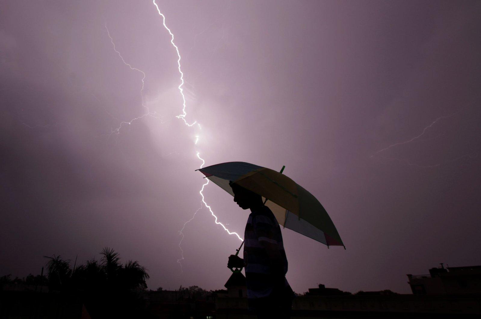 A pedestrian walks with an umbrella as lightning strikes during an evening thunderstorm in Jammu, India, May 15, 2015. (AFP Photo)