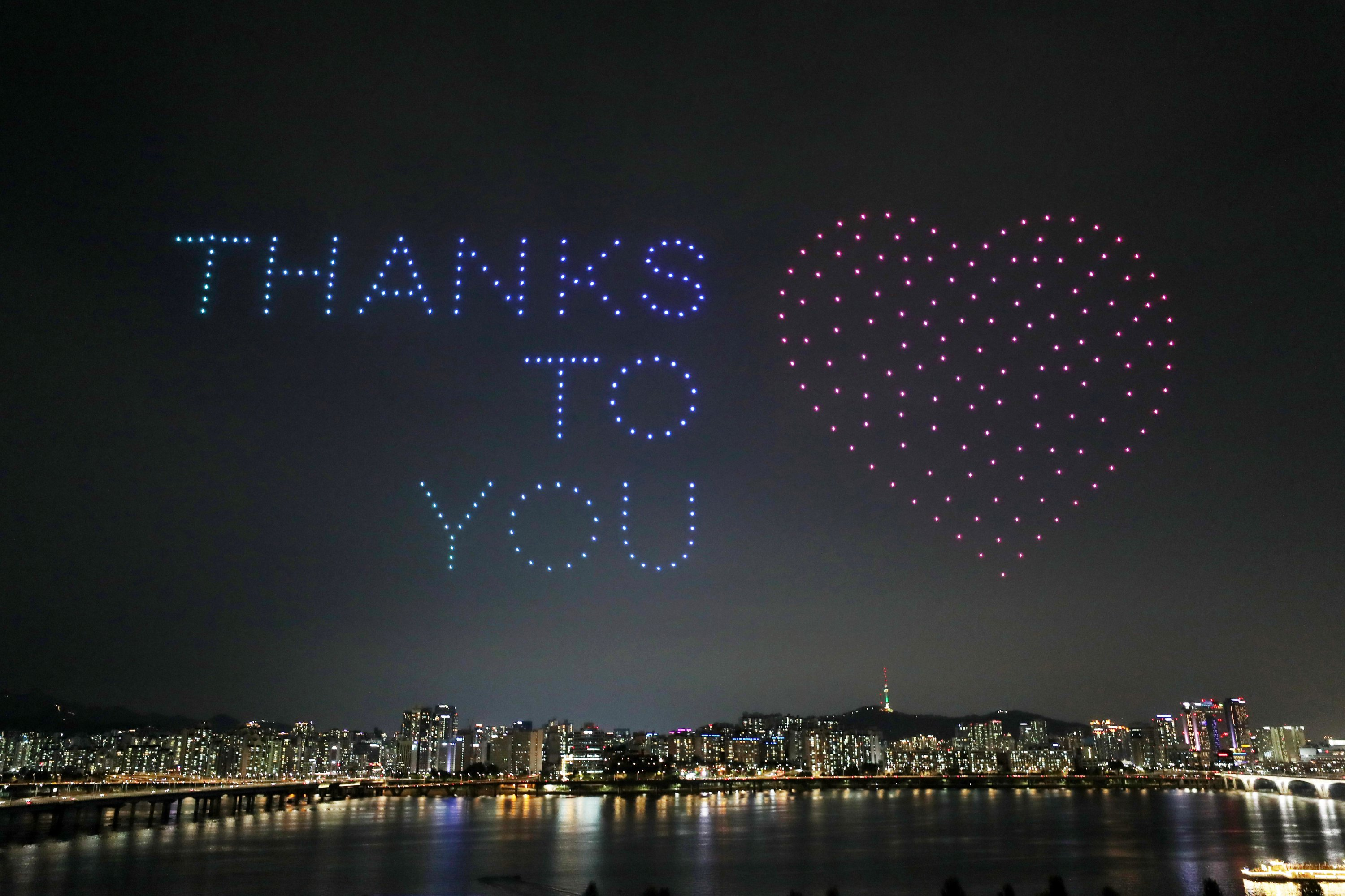 Drones fly over the Han river showing messages to support the country as a measure to avoid the spread of the coronavirus continues in Seoul, South Korea, July 4, 2020. (Yonhap via Reuters)