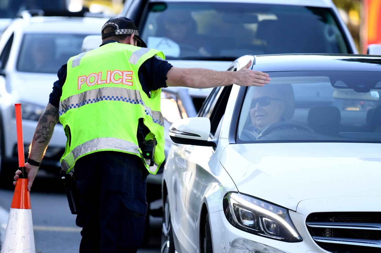 A police officer directs a car for further inspection at a checkpoint on the Queensland-New South Wales state border in Coolangatta on the Gold Coast, Queensland, Australia, July 1, 2020. (EPA Photo)