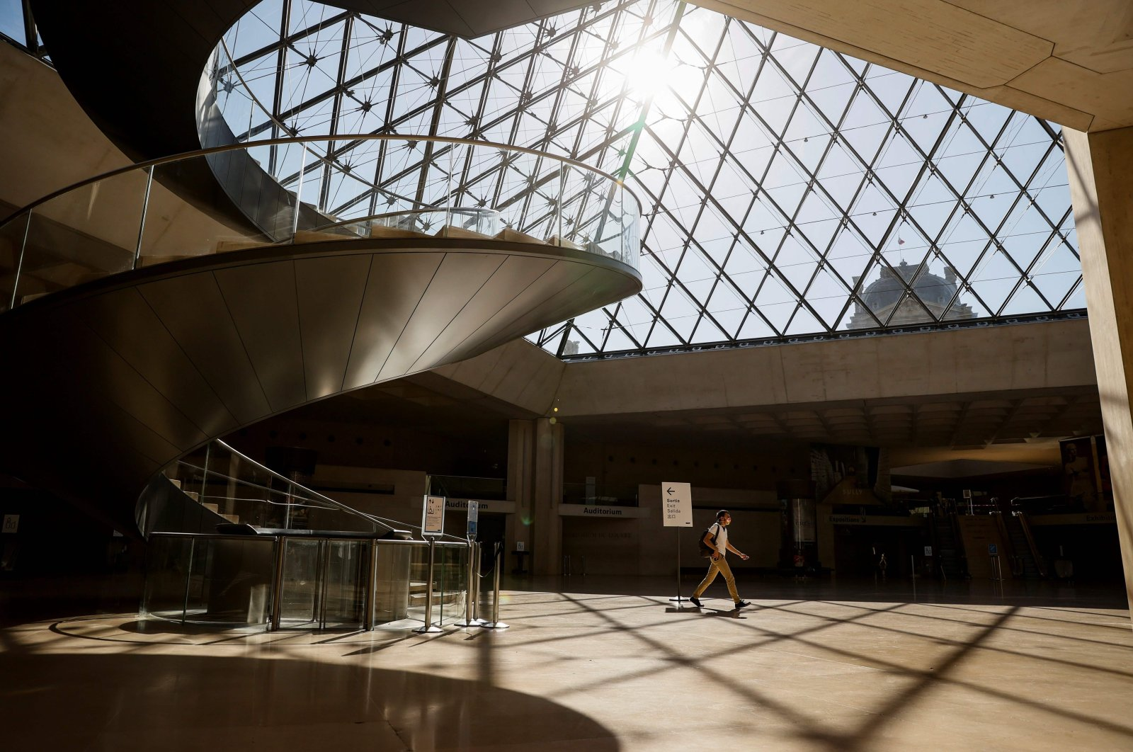 An employee passes under the Louvre pyramid designed by Chinese architect Ieoh Ming Pei near the Louvre Museum in Paris, France, June 23, 2020. (AFP Photo)