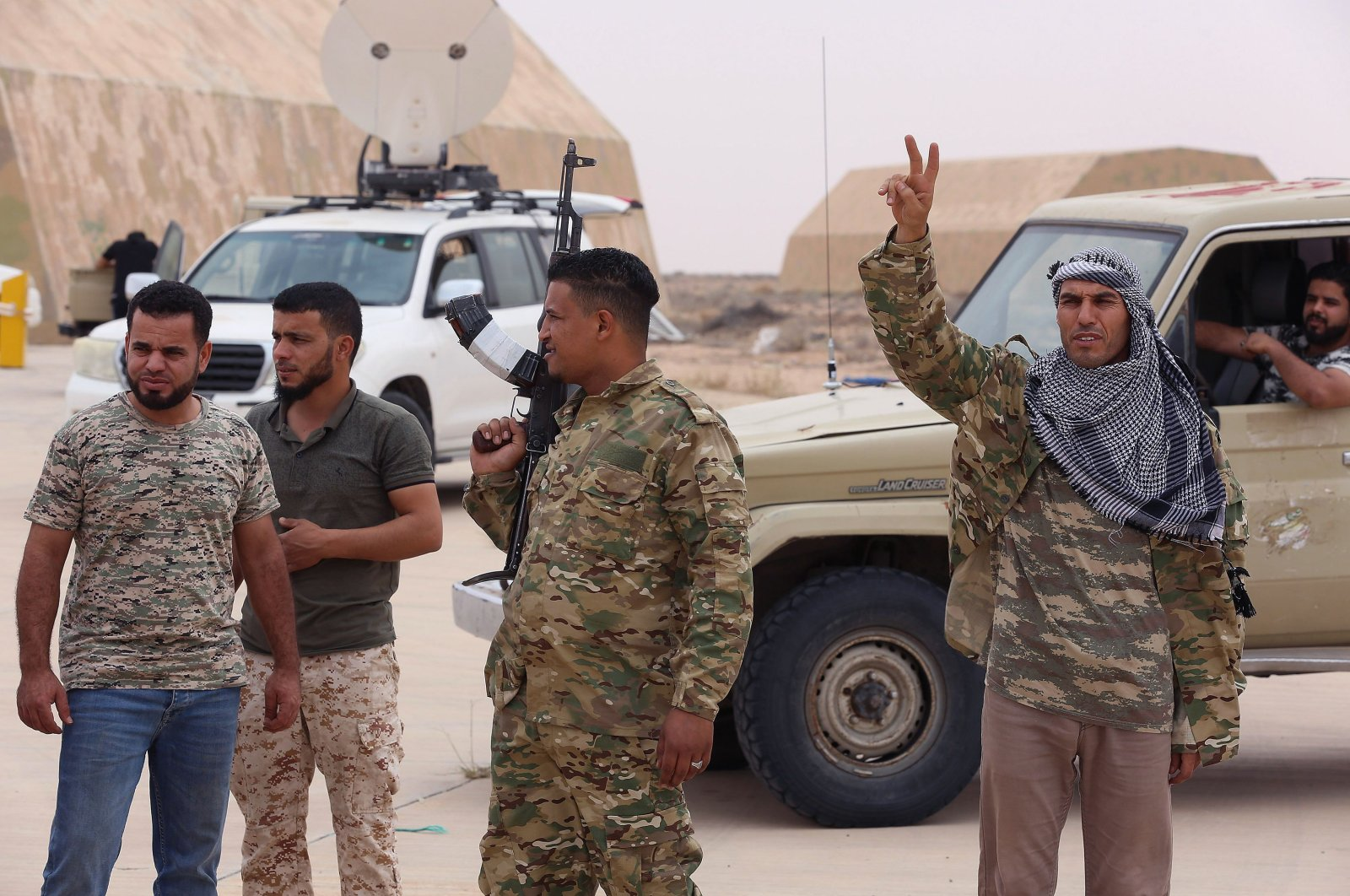 Fighters loyal to Libya's U.N.-recognized Government of National Accord (GNA) stand outside a hangar at al-Watiya airbase, May 18, 2020. (AFP Photo)