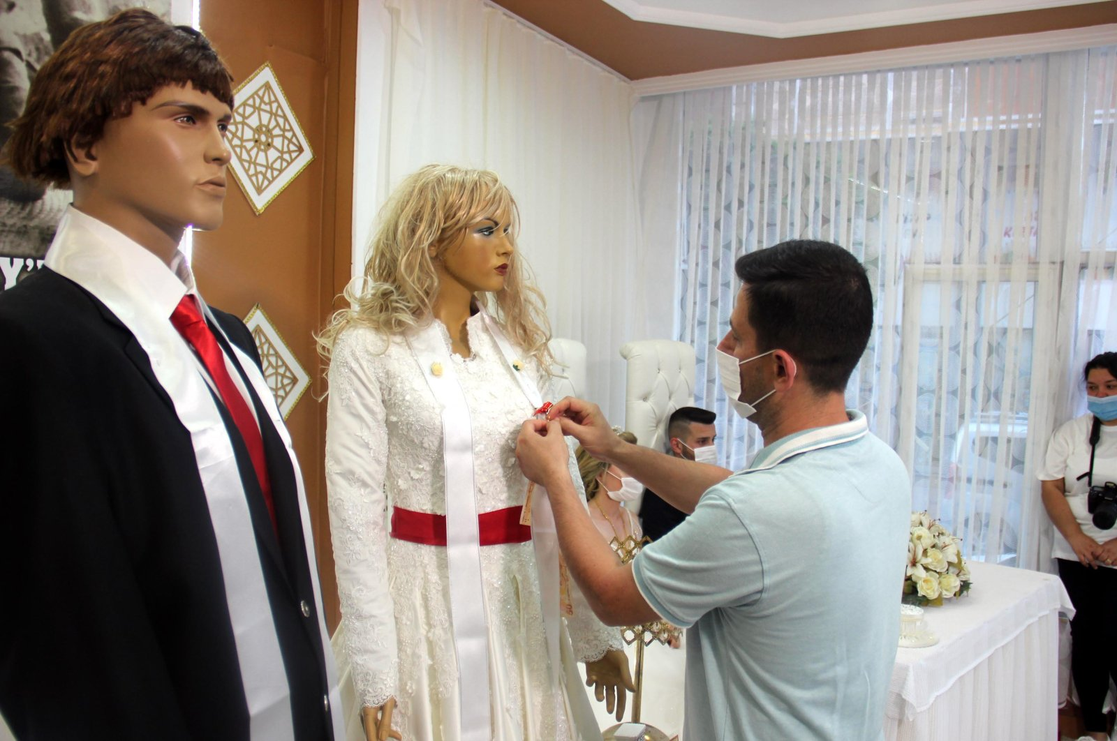 A guest attaches his gift to a dummy bride while the real couple sits at a table, Tekirdağ, Turkey, July 5, 2020. (DHA Photo)