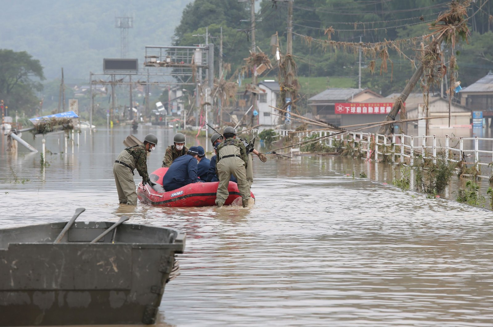Japan Self-Defense Forces and police officers handle an inflatable boat to join rescue operations at a nursing home following heavy rain in Kuma village, Kumamoto prefecture, July 5, 2020. (AFP Photo)