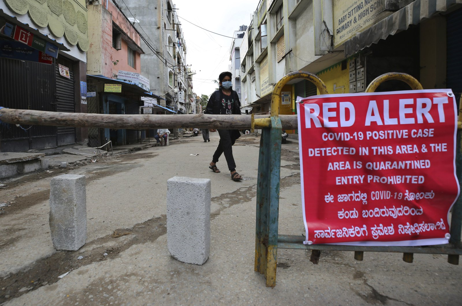 A boy wearing a face mask as a precaution against the coronavirus walks past a notice displayed in a containment zone, Bengaluru, July 5, 2020. (AP Photo)