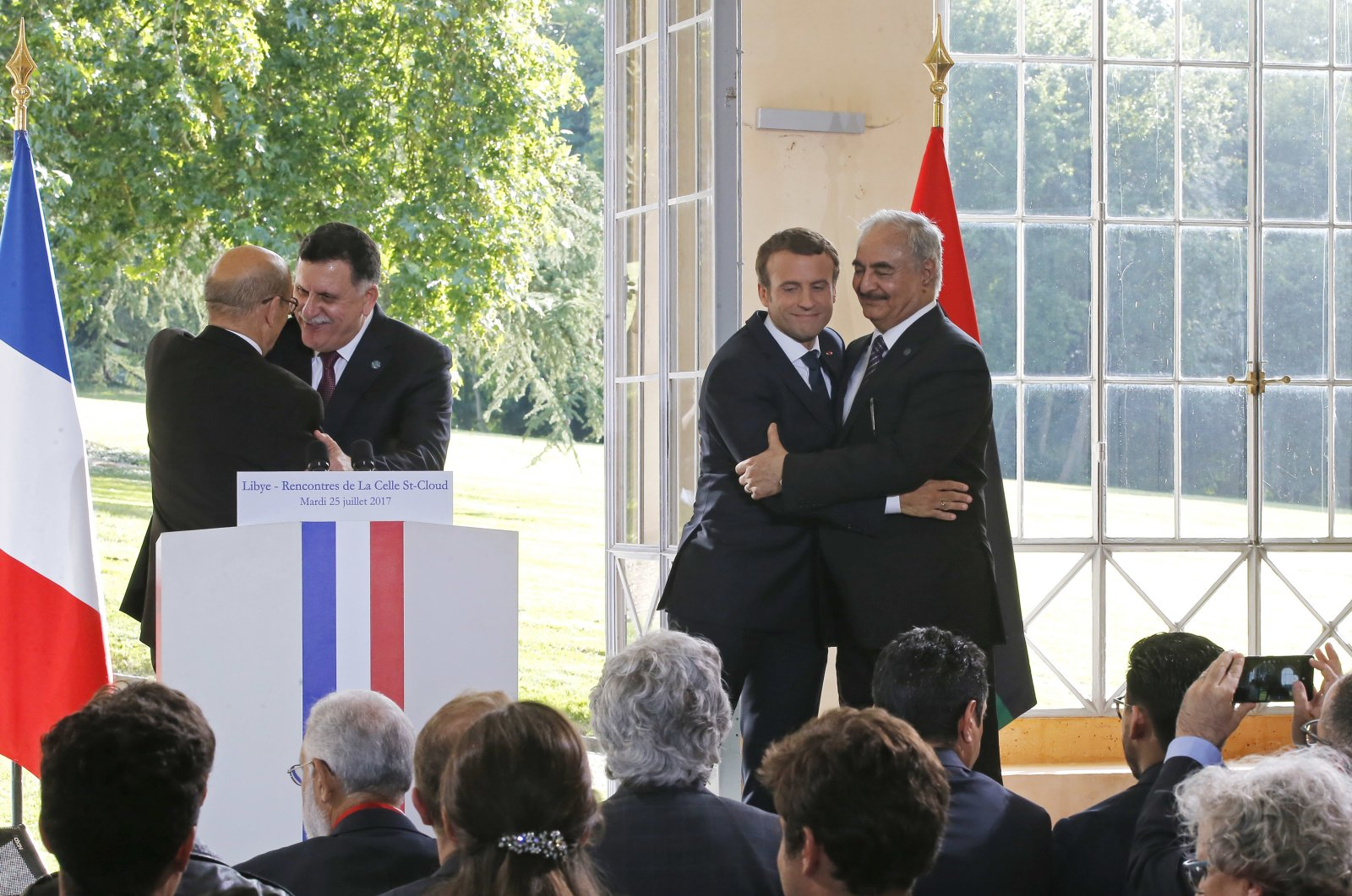 Libyan Prime Minister Fayez Sarraj (L) and French Foreign Minister Jean-Yves Le Drian (2nd from L), and French President Emmanuel Macron (2nd from R) and putschist Gen. Khalifa Haftar (R) hug each other after a news conference at the Chateau of the La Celle-Saint-Cloud, west of Paris, France, July 25, 2017. (AP Photo)