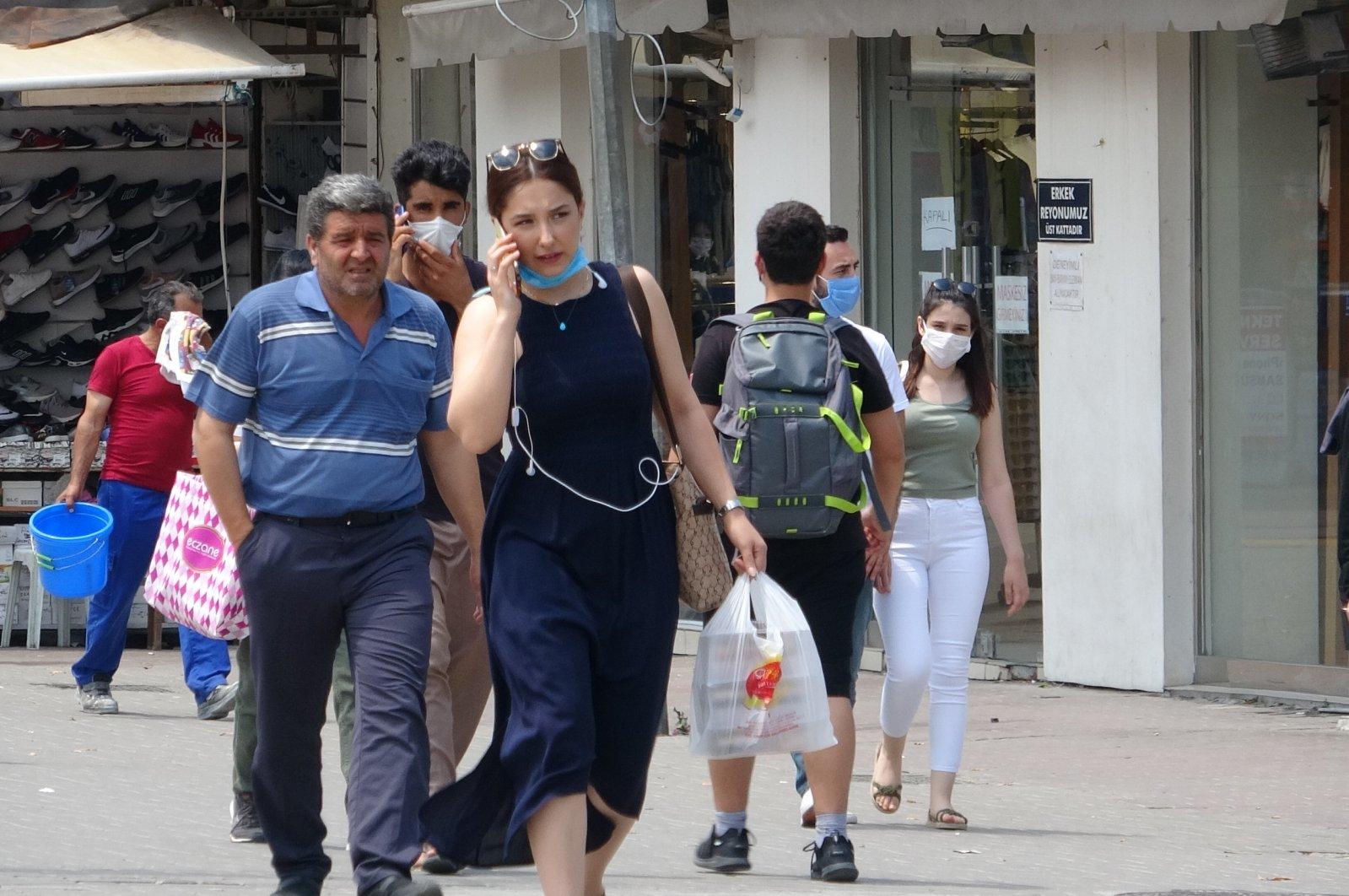 People wearing masks and those not wearing masks walking on a street in Bursa, Turkey, July 6, 2020. (DHA Photo)