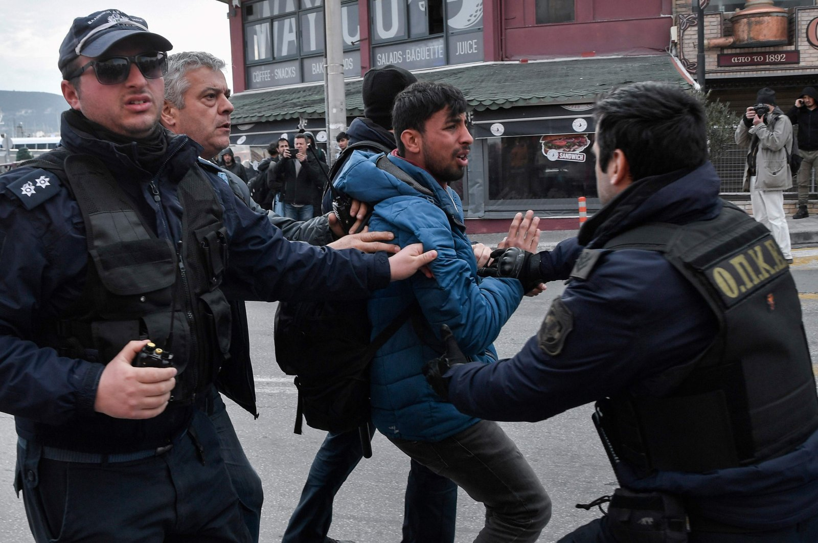 Greek police detain a migrant man while they try to push back migrants and refugees from the Moria camp who gathered outside the port of Mytilene on the island of Lesbos, hoping to get a ferry to Athens, March 4, 2020. (AFP)