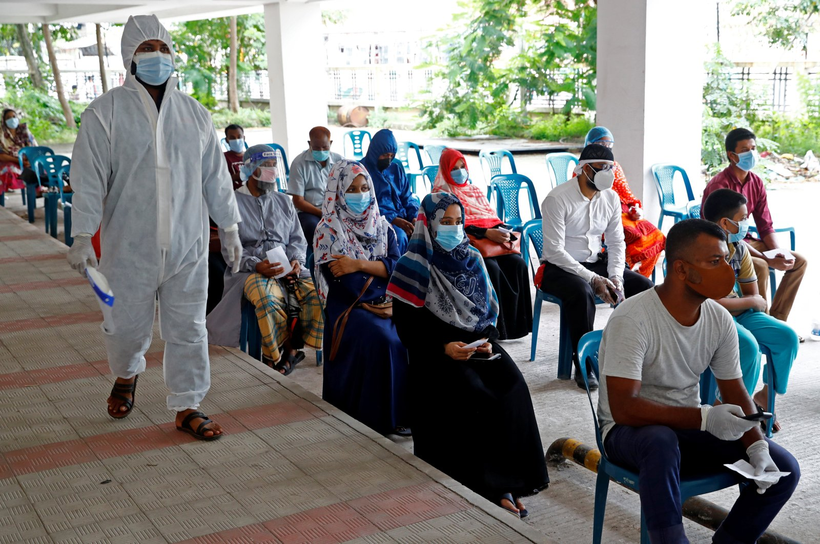 People sit as they come to a coronavirus testing center in the Mugda Medical College and Hospital as the coronavirus outbreak continues in Dhaka, Bangladesh, July 2, 2020. (REUTERS)