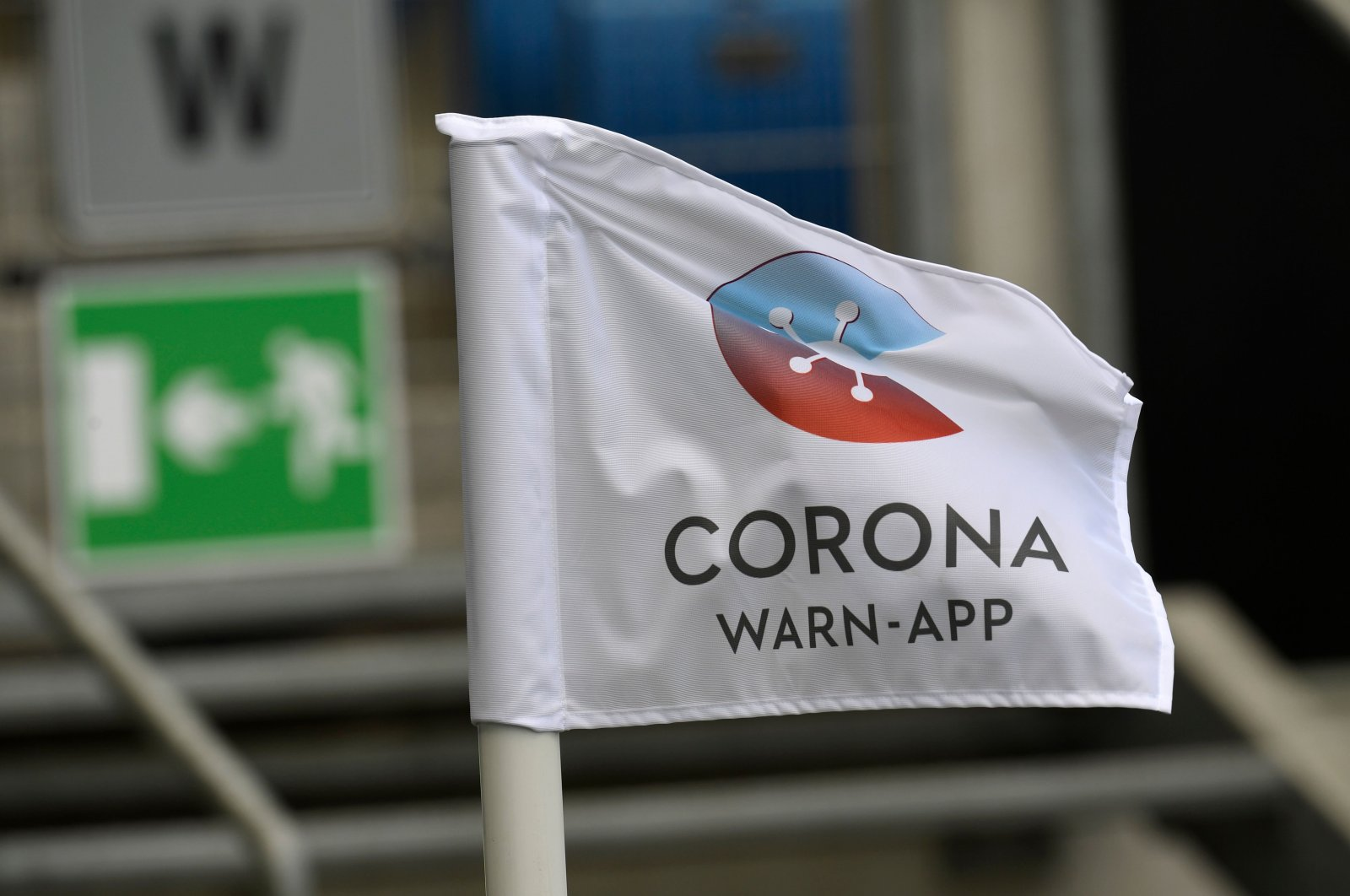 """A flag with the logo of Germany's official """"Corona Warn-App"""" contact tracing app is seen at the stadium prior to the German first division Bundesliga football match TSG Hoffenheim v FC Union Berlin in Sinsheim, southwestern Germany, on June 20, 2020. (AFP Photo)"""