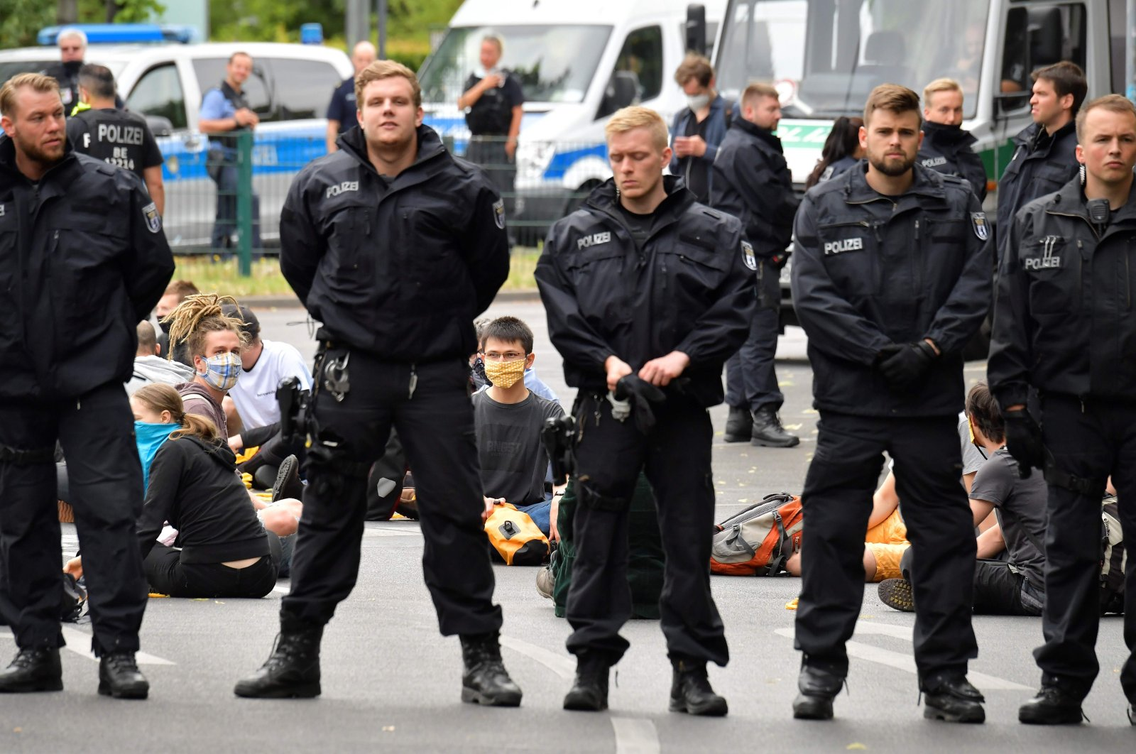 Policemen stand in front of demonstrators staging a protest against the government's coal phase-out law in front of Germany's Social Democratic Party headquarters, Berlin, July 1, 2020. (AFP File Photo)
