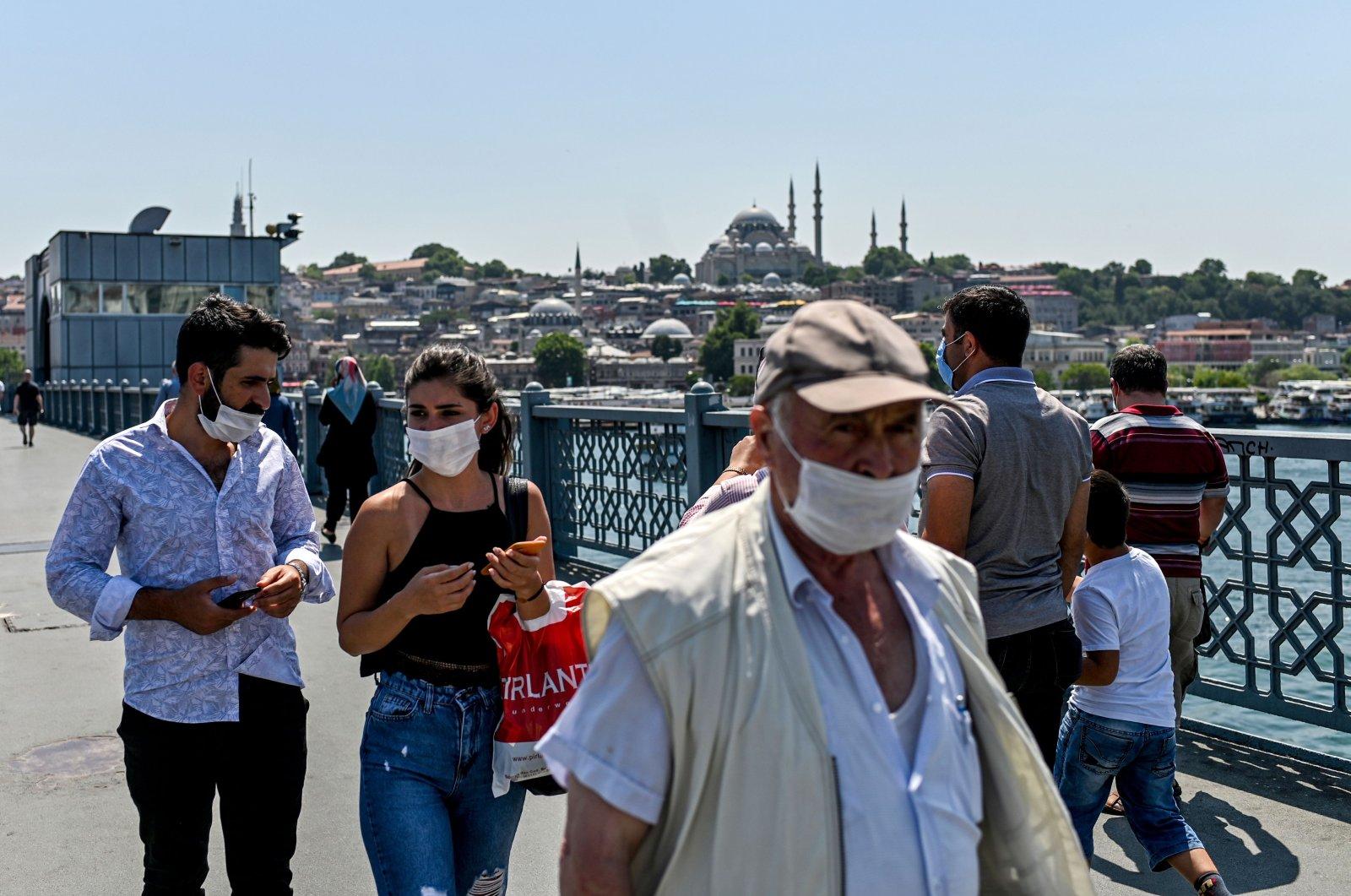 People wearing protective face masks walk on the Galata Bridge, Istanbul, Turkey, July 1, 2020. (AFP Photo)