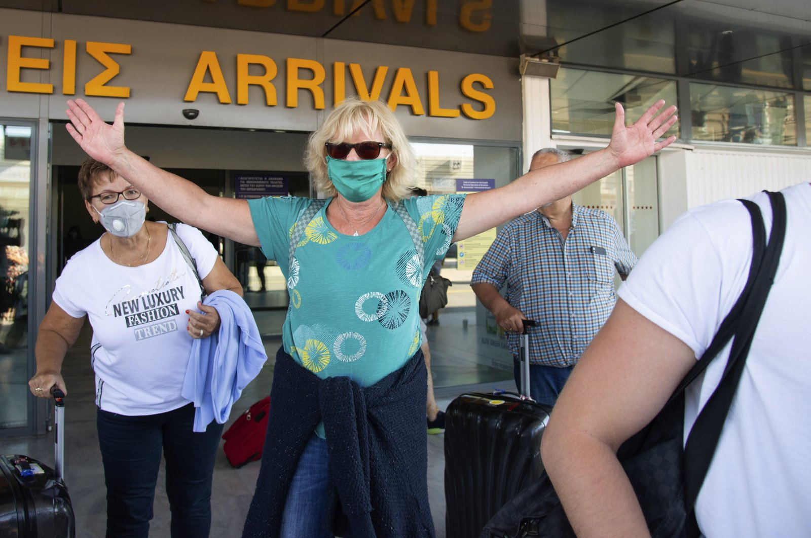 A tourist reacts as she arrives with others at Nikos Kazatzakis International Airport in Heraklion, Crete island, Greece, July 1, 2020. (AP Photo)